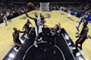 Spurs' Duncan goes to the basket past Miami's Miller during Game 5 of the NBA Finals in San Antonio