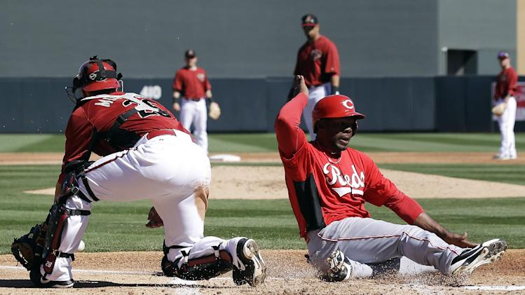 Cincinnati Reds' Denis Phipps, right, scores past Arizona Diamondbacks catcher Miguel Montero, left, after a sacrifice fly from Neftali Soto during the second inning of an exhibition spring training baseball game, Wednesday, Feb. 27, 2013, in Scottsdale, Ariz. (AP Photo/Marcio Jose Sanchez)