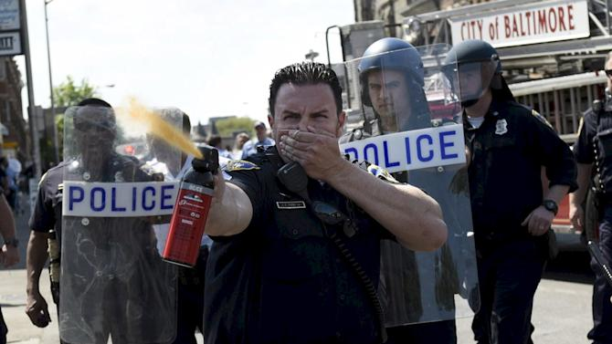 A law enforcement officer uses pepper spray to disperse the crowd at the intersection of North and Pennsylvania Avenues in Baltimore