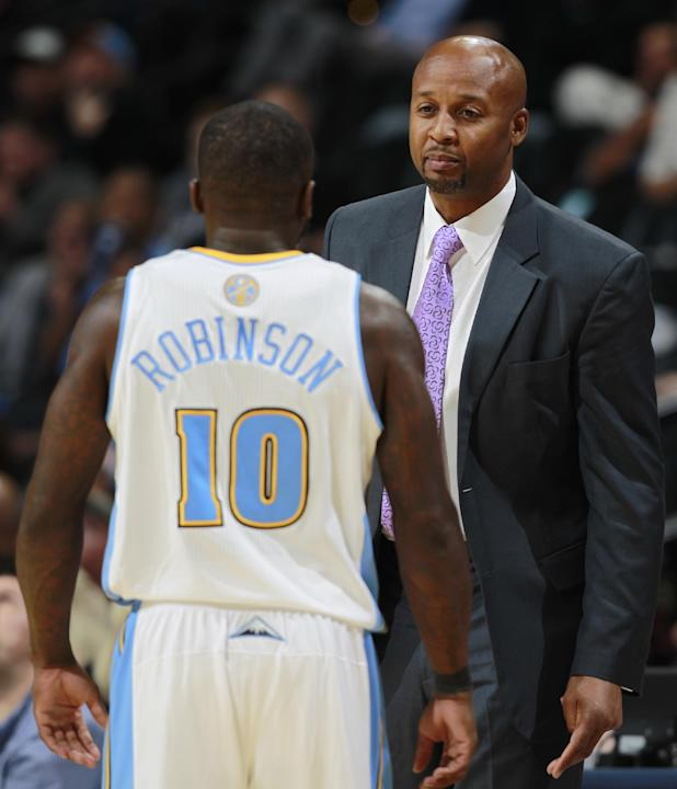 Denver Nuggets head coach Brian Shaw, back, confers with guard Nate Robinson while facing San Antonio Spurs in the fourth quarter of the Nuggets' 98-94 victory in an NBA preseason basketball game in D
