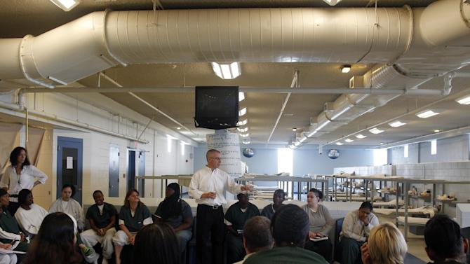 FILE - FILE - In this Tuesday, Aug. 2, 2011 file photo, former New Jersey Gov. James McGreevey, center, listens as an inmate speaks to a gathering of women inmates at Integrity House, a transitional housing and residential treatment area for women incarcerated at the Hudson County Correctional Center, in Kearney, N.J. The jailhouse treatment program where McGreevey works has earned a spot at the Sundance Film Festival and accolades from the U.S. Justice Department. McGreevey is spiritual counselor to 40 women in a pilot program to keep them from returning to jail. The Justice Department cites the program as one of two top re-entry efforts nationwide. The struggles of the women as well as McGreevey's own admission that he is gay and resignation as governor are the subject of a documentary showing at the Sundance Film Festival in January.  (AP Photo/Mel Evans, File)