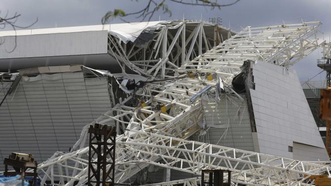 "Workers stand next to a crane that collapsed on the site of the Arena Sao Paulo stadium, known as ""Itaquerao"", which will host the opening soccer match of the 2014 World Cup, in Sao Paulo"