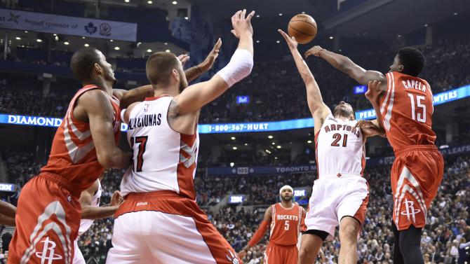 Houston Rockets' Clint Capela (15) and Toronto Raptors' Greivis Vasquez (21) fight for the ball during the first half of an NBA basketball game in Toronto, Monday, March 30, 2015. (AP Photo/The Canadian Press, Frank Gunn)