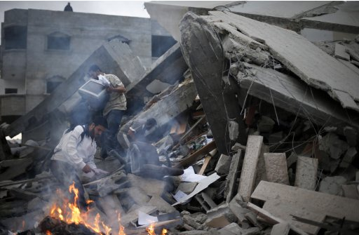Palestinians inspect the destroyed office building of Hamas PM Haniyeh in Gaza