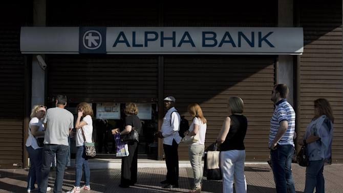 People line up outside an Alpha bank branch to use ATM machine, in Athens, on Tuesday, June 30, 2015. With banks shut and Greeks limited to cash withdrawals of 60 euros ($67) per day, long lines formed once more at ATM machines. Capital controls began Monday and will last at least a week, after a weekend bank run prompted by the prime minister's call for a referendum on creditor demands in return for bailout loans. (AP Photo/Petros Giannakouris)