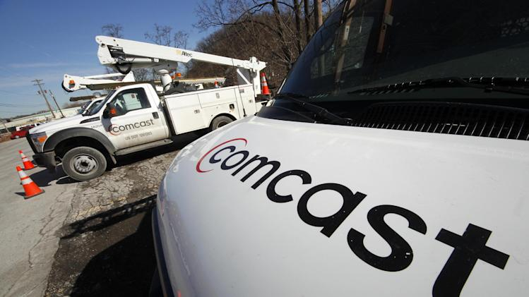 FILE - In this Feb. 15, 2011 file photo, Comcast logos are displayed on installation trucks in Pittsburgh. Federal regulators announced Tuesday, Oct. 16, 2012 that they are letting cable companies scramble all their TV signals, closing a loophole that lets many households watch basic cable channels for free.  (AP Photo/Gene J. Puskar, file)