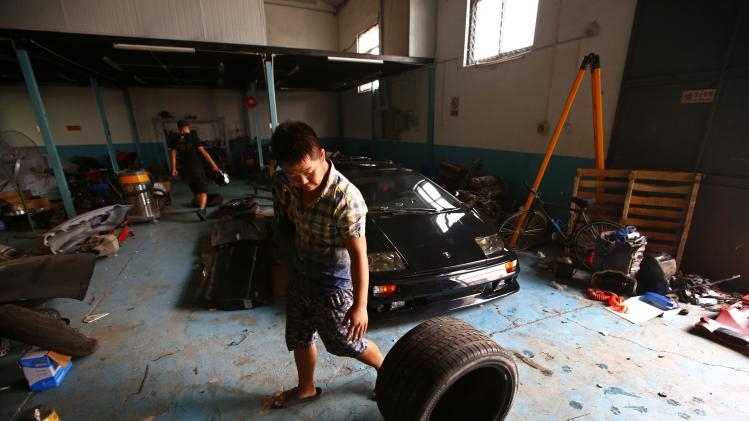 A worker rolls a tyre in front of a handmade replica of Lamborghini Diablo at a garage rented by Wang and Li on the outskirts of Beijing