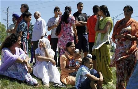 Members of the Sikh Temple wait for news following a mass shooting in Oak Creek, Wisconsin