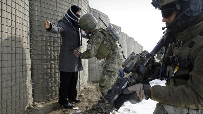 In this Monday, Jan. 14, 2013 photo, a female member of Afghan special forces, center, searches a woman during a training exercise on the outskirts of Kabul, Afghanistan. Afghanistan's army is training female special forces to take part in night raids against insurgents despite cultural taboos as foreign combat troops take the backseat ahead of their eventual departure at the end of 2014. In a country where women traditionally are expected to stay home, their participation in the special forces is breaking new ground in ultraconservative Afghanistan. (AP Photo/Musadeq Sadeq)