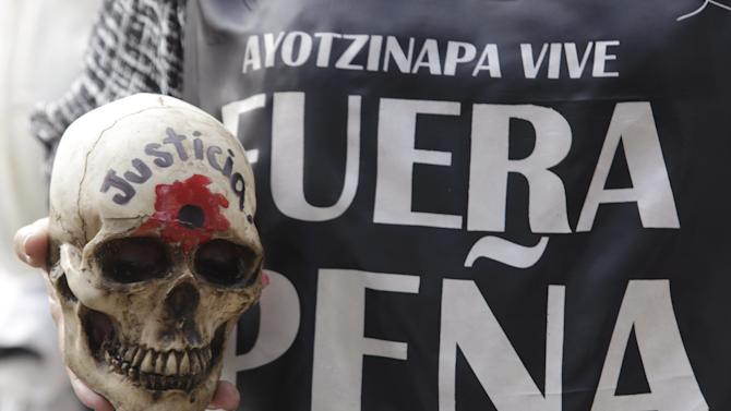 A woman holds up a skull as she takes part in a march to mark the 14-month anniversary of the disappearance of the students from Ayotzinapa College Raul Isidro Burgos, in Mexico City