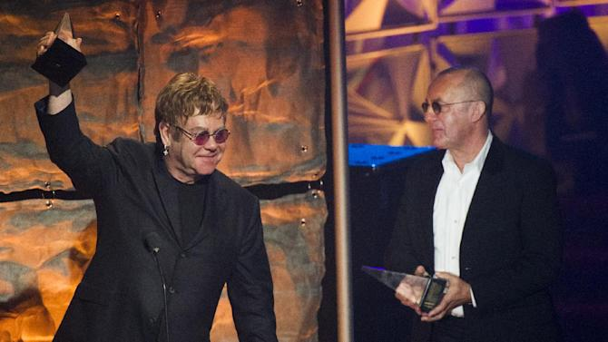 """Elton John, left, and Bernie Taupin accept the """"Johnny Mercer"""" award at the Songwriters Hall of Fame 44th annual induction and awards gala on Thursday, June 13, 2013 in New York. (Photo by Charles Sykes/Invision/AP)"""
