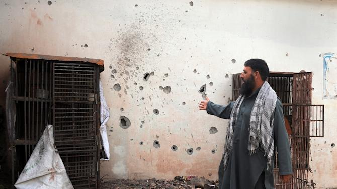 A Pakistani Kashmiri man points to a damaged wall hit by a mortar during cross border shelling, in Nakyal Sector, on the heavily militarised Line of Control (LoC) in Pakistan-administered Kashmir, on August 18, 2015