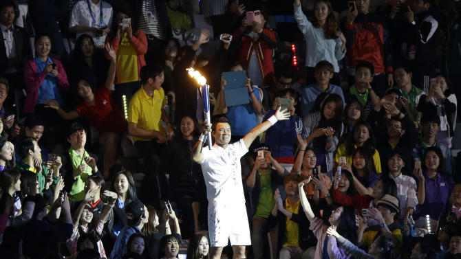South Korean baseball player Lee Seung-yeop holds the Asian Games flame during the opening ceremony for the 17th Asian Games in Incheon, South Korea,Friday, Sept. 19, 2014