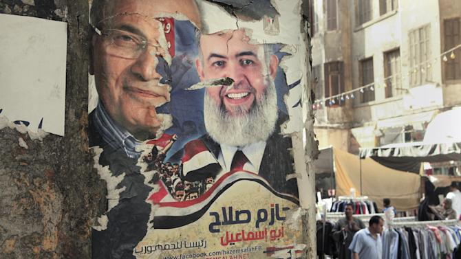 "A defaced poster of Presidential candidate for the upcoming elections Ahmed Shafiq, left, and disqualified Egyptian presidential hopeful Muslim cleric Hazem Salah Abu Ismail in Cairo, Egypt, Thursday, April 26, 2012. Egypt's election commission announced the final list of 13 candidates this week for next month's presidential elections. Arabic on the poster reads, ""Hazem Salah for Egyptian Presidency."" (AP Photo/Amr Nabil)"