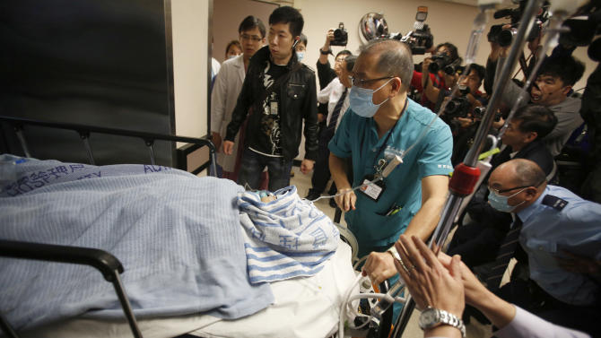 """Medical staffs escort former Ming Pao chief editor Kevin Lau on a stretcher in a hospital in Hong Kong, China Wednesday, Feb. 26, 2014. The former editor of the Hong Kong newspaper whose abrupt dismissal in January sparked protests over press freedom has been stabbed, police said on Wednesday. Police said a man wearing a motorcycle helmet """"suddenly"""" attacked Kevin Lau on Wednesday morning with a knife and then fled on a motorcycle driven by another man. (AP Photo)"""