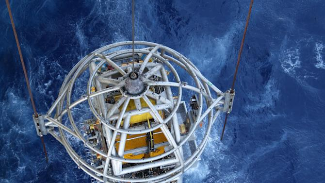 In this Oct. 27, 2011 photo, an underwater robot is lowered into the water to work on equipment on the sea floor, 8,000 feet below. Two hundred miles off the coast of Texas, ribbons of pipe are reaching for oil and natural gas deeper below the ocean's surface than ever before. (AP Photo/Jon Fahey)