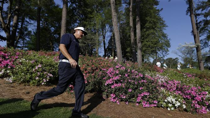 Phil Mickelson walks down the sixth fairway past blooming azaleas during a practice round for the Masters golf tournament Tuesday, April 9, 2013, in Augusta, Ga. (AP Photo/Darron Cummings)
