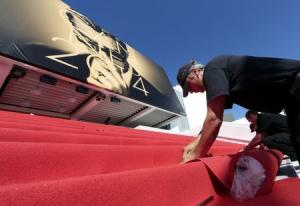 Workers install the red carpet in front of the main entrance of the Festival Palace for the opening ceremony of the 67th Cannes Film Festival in Cannes