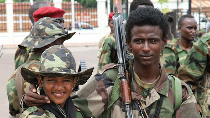 In this March 27, 2013 photo, young soldiers from the Seleka rebel alliance pose for a photo as they stand amidst their fellow soldiers at the Ledger Plaza Bangui hotel, in Bangui, Central African Republic. The United Nations children's agency warns that it has 'clear evidence of the continuing recruitment and use of children by armed groups' in Central African Republic. An Associated Press reporter saw dozens of youths among the ranks of the Seleka fighters in the capital, more than three weeks after the insurgents caused the president to flee the country. Child soldiers were even used in some of the heaviest fighting in the battle for Bangui. (AP Photo)