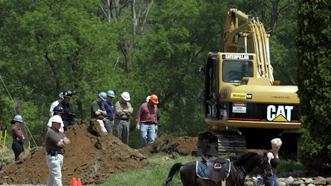 FILE - In this May 25, 2006, file photo, excavation crews dig up the site of a horse barn that was demolished as part of the FBI's search for the remains of Jimmy Hoffa in Milford Township, Mich. (AP Photo/Carlos Osorio, File)