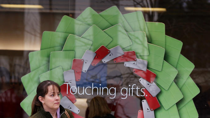 """A shopper carries a bag past a holiday display at the Apple Store at the Derby Street Shoppes in Hingham, Mass. Friday, Dec. 7, 2012. This holiday shopping season, stores haven't been offering the same big discounts as they did in previous years as they tried to lure shoppers in with other incentives,but during the final days leading up to Christmas, shoppers will see more of those jaw-dropping """"70 percent off"""" sale signs as stores try to salvage a season that so far has been disappointing. (AP Photo/Stephan Savoia)"""