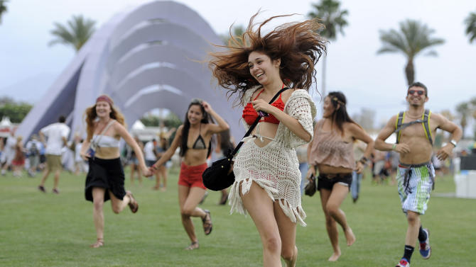 FILE - This April 13, 2012 file photo shows festivalgoers running toward the main stage to catch the beginning of Kendrick Lamar's set during the first weekend of the 2012 Coachella Valley Music and Arts Festival in Indio, Calif. Despite heat, humidity, crowds and costs, music festivals are more popular than ever, attracting millions of fans, with 270 festivals of various types annually in the U.S. and more than 800 in 57 countries. (AP Photo/Chris Pizzello, file)