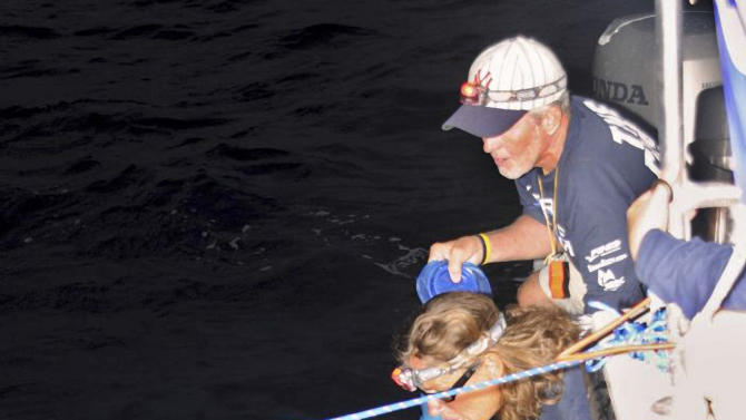 In this photo provided by the Florida Keys News Bureau, endurance swimmer Diana Nyad receives hydration and advice from her support team off Havana, Cuba, Saturday, Aug. 18, 2012, during the first night of a 100-mile-plus swim across the Florida Straits to the Florida Keys. Nyad, who turns 63 on Aug. 22, is trying to be the first swimmer to cross the Straits without a shark cage. (AP Photo/Diana Nyad, via the Florida Keys News Bureau, Christi Barli)