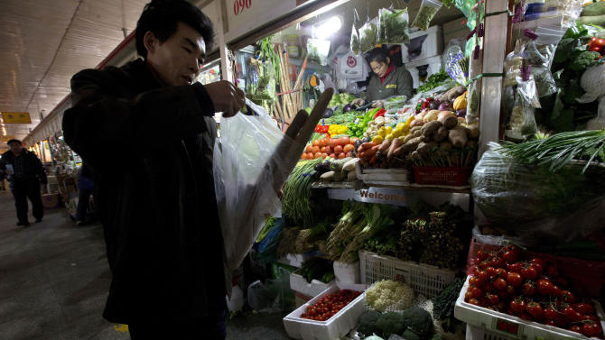 A Chinese man bundles vegetables in a plastic bag at a market in Beijing Friday, Jan. 11, 2013. China's inflation spiked to a six-month high in December after a freezing winter pushed up vegetable prices, possibly complicating efforts to sustain a shaky economic recovery, the National Bureau of Statistics reported Friday. (AP Photo/Ng Han Guan)