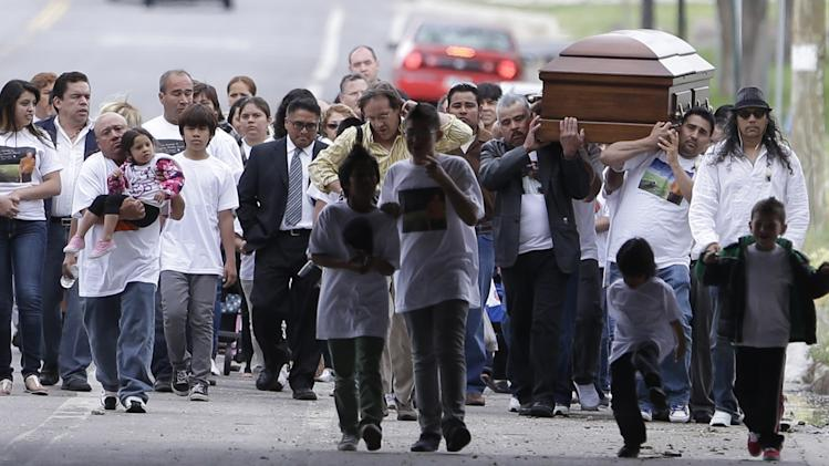 Mourners carry the casket of Ricardo Portillo along a street following a public wake to the funeral service at Our Lady of Guadalupe Church Wednesday, May 8, 2013, in Salt Lake City. People attend a funeral services to honor a Utah soccer referee who was punched by a player and later died after a weeklong coma. Portillo died Saturday, a week after police say a 17-year-old player struck him in the head during a recreational league soccer game after the referee called a penalty against him. (AP Photo/Rick Bowmer)