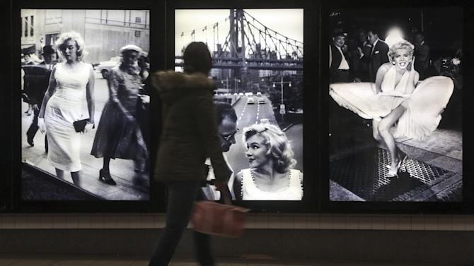 "A commuter inspects the Sam Shaw's photographs during the ""Marilyn in New York"" exhibit  at the 42nd St. subway station for the B,D,F,M and 7 lines, Thursday, Dec. 20, 2012 in New York. The exhibit is part of the Metropolitan Transportation Authority's ""Arts for Transit"" program. The show opened Thursday and will be up for a year. (AP Photo/Mary Altaffer)"