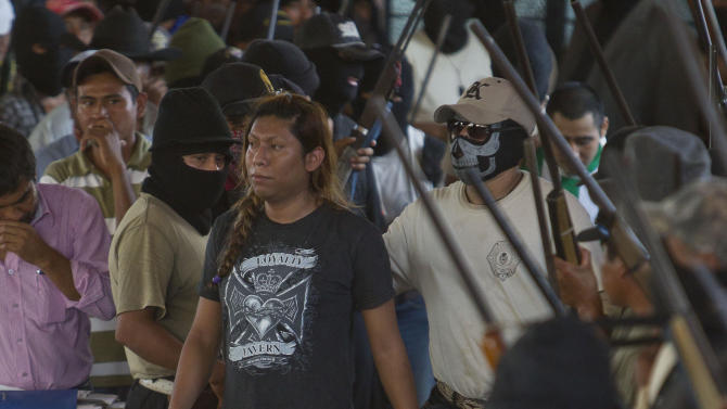 Masked members of the community of Ayutla escort a detained person to a community assembly in the town of El Meson, Mexico, Thursday Jan. 31, 2013. Vigilantes who have taken up arms against drug cartel violence and common crime in southern Mexico brought charges ranging from organized crime to kidnapping and extortion against 50 men and three women who they have been holding prisoner at improvised jails, in some cases for weeks. (AP Photo/Christian Palma)