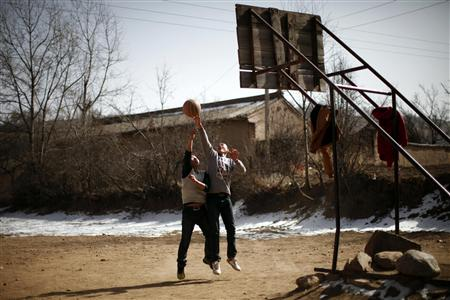 Teenagers play basketball in Yuangudui village, Gansu Province
