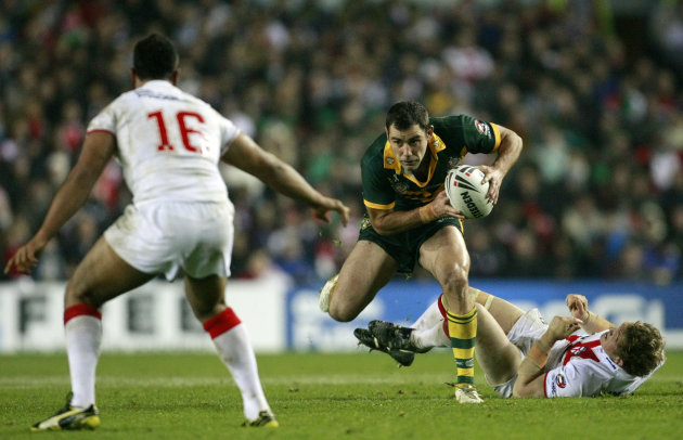 Australia's Cameron Smith, center, runs at England's Jamie Jones-Buchanan, left, during the four nations rugby league final at Elland Road, Leeds, England, Saturday Nov. 19, 2011. (AP Photo/Tim Hales)