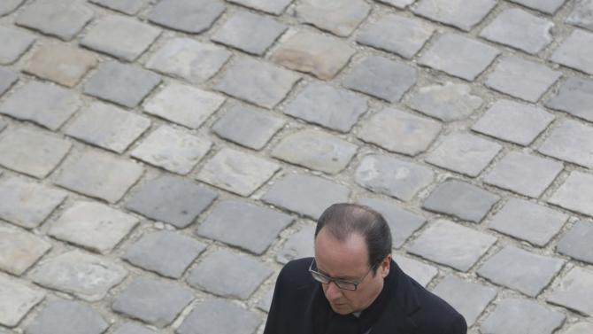 French President Francois Hollande leaves after a ceremony to pay a national homage to the victims of the Paris attacks at Les Invalides monument in Paris