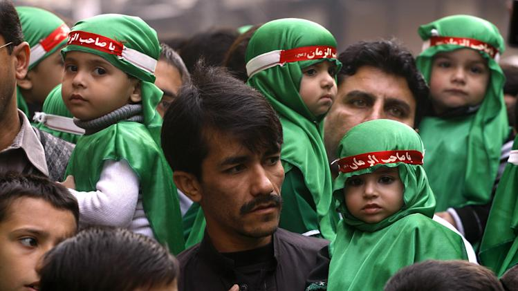 Pakistani Shiite Muslims carry children in a procession to mark Muharram in Peshawar, Pakistan on Friday, Nov. 23, 2012. Muharram is a month of mourning in remembrance of the martyrdom of Imam Hussein, the grandson of Prophet Mohammed. (AP Photo/Mohammad Sajjad)