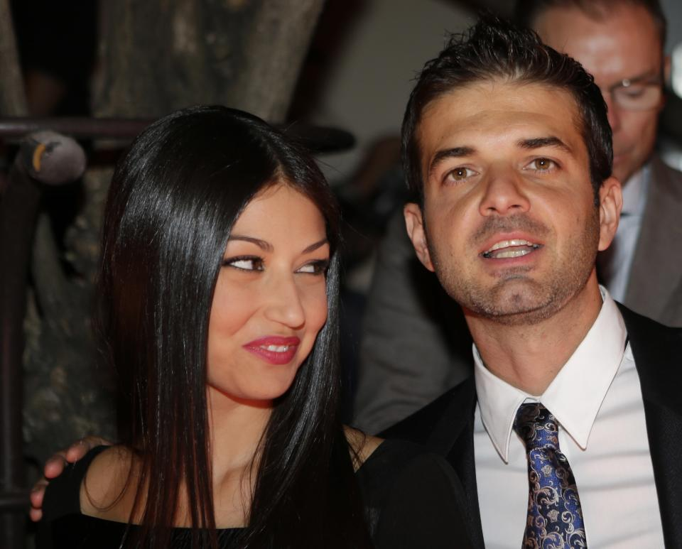 Inter Milan coach Andrea Stramaccioni is flanked by his wife Dalila as they attend the Versace women's Fall-Winter 2012-2013 collection that was presented in Milan, Italy, Friday Sept. 21, 2012.(AP Photo/Luca Bruno)