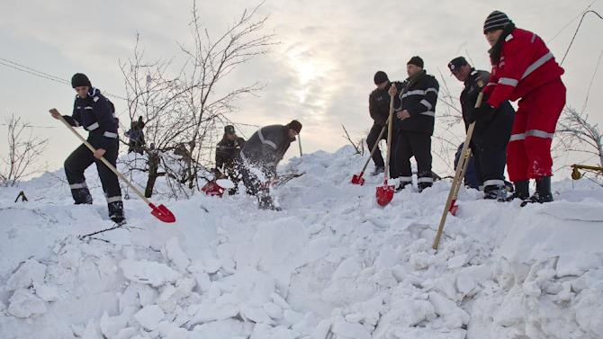 Firefighters and emergency services workers dig in high snow to clear the access to a snowed in house in the village of Silistea Glodeanu, Romania, Tuesday, Feb. 14, 2012 the day after more snow storms hit the area.Snow as deep as 15 feet (4.5 meters) isolated areas of Romania, Moldova and Albania on Tuesday, and helicopters and army trucks were used to deliver food and medicine, and to transport sick people to hospitals.(AP Photo/Vadim Ghirda)