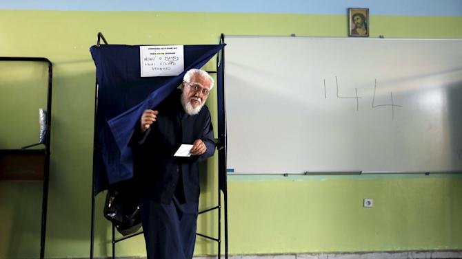 Greek Orthodox priest exits a booth at a polling station  in Athens