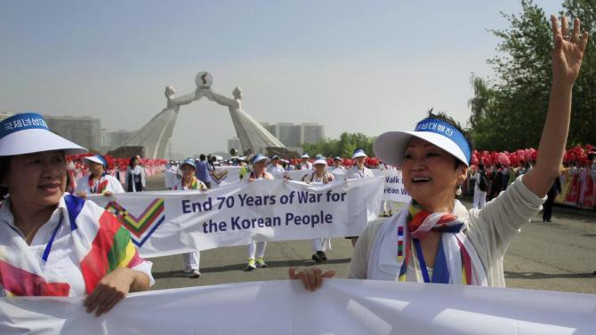 Aiyoung Choi, right, waves as she and a group of peace activists including Gloria Steinem, (not pictured), an iconic figure in the equal rights movement in the United States, march at the Three Charters for National Reunification Memorial Tower, Saturday, May 23, 2015, in Pyongyang, North Korea. They planned to march across the Demilitarized Zone and hope that it would bring world attention to calls for a resolution to tensions on the Korean Peninsula. (AP Photo/Jon Chol Jin)