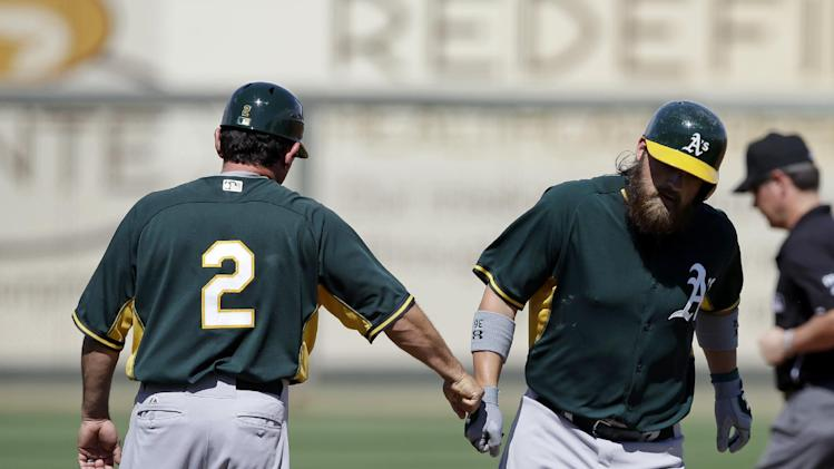 Oakland Athletics' Derek Norris is congratulated by third base coach Mike Gallego (2) after hitting a three-run home run during the second inning of a spring exhibition baseball game against the Kansas City Royals, Friday, March 14, 2014, in Surprise, Ariz