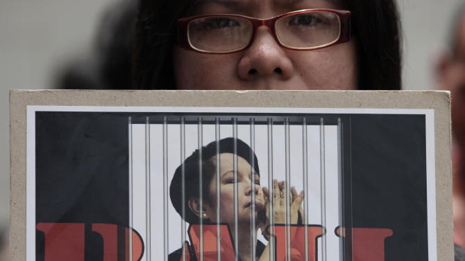 An activist holds a slogan with a picture of former Philippine President Gloria Macapagal Arroyo as they await her release outside a government hospital in suburban Quezon City, north of Manila, Philippines, Wednesday July 25, 2012. Arroyo on Wednesday walked out of a government hospital where she has been detained for nearly eight months on charges of election sabotage after a court found that evidence against her was weak and granted bail. (AP Photo/Aaron Favila)