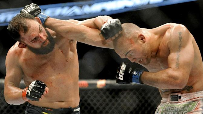 Johny Hendricks, left, and Robbie Lawler exchange punches during a UFC 171 mixed martial arts welterweight title bout, Saturday, March 15, 2014, in Dallas. Hendricks won by decision