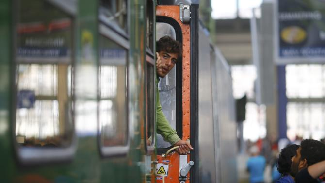 A migrant looks from a train at the Keleti train station in Budapest