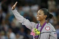 US gymnast Gabrielle Douglas celebrates on the podium after winning the artistic gymnastics women's individual all-around final at the 02 North Greenwich Arena in London during the London 2012 Olympic Games. Douglas won ahead of Viktoria Komova and Aliya Mustafina