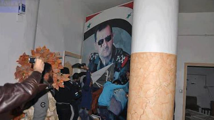 FILE - In this Monday, March. 4, 2013 file Citizen journalism image provided by Coordination Committee in Kafr Susa which has been authenticated based on its contents and other AP reporting, shows people tearing down a huge poster of President Bashar Assad and hitting it with their shoes, in Raqqa, Syria. Since Raqqa fell under rebel control last week, opposition fighters have posted guards at government buildings to prevent looting, brought down the price of bread and opened a telephone hotline for residents to report security problems. Raqqa is shaping up as a test case for how rebels will administer their areas. (AP Photo/Coordination Committee In Kafr Susa, File)