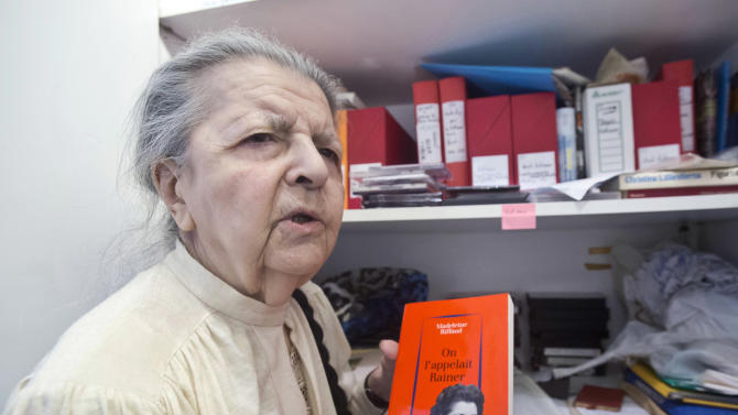 This Tuesday Aug. 19, 2014 photo shows French poet, journalist, and a member of the French Resistance Madeleine Riffaud answering a reporter during an interview with the Associated Press in Paris. She holds a book she wrote, with on the cover, a photo of her at the time of WWII. She had a code name, Rainer, and a gun she called Oscar. Just weeks before turning 20, she aimed her weapon at a Nazi officer and shot him dead on a Paris bridge. (AP Photo / Michel Euler)