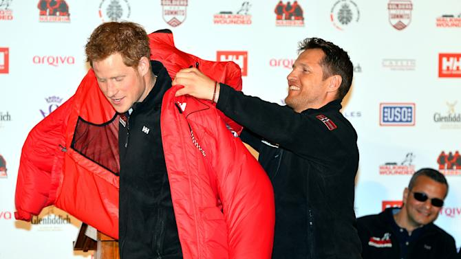Prince Harry is presented with a red thermal coat during the launch event of the Walking With The Wounded South Pole Allied Challenge 2013 at the Mandarin Oriental Hotel, London, Friday April 19, 2013. Prince Harry will take part in a race to the South Pole with a team of wounded British servicemen and women, he announced today. The 28-year-old will take on teams from the United States and the Commonwealth in the 208-mile (335km) Walking With The Wounded South Pole Allied Challenge in November and December this year.(AP Photo, PA, John Stillwell) UNITED KINGDOM OUT