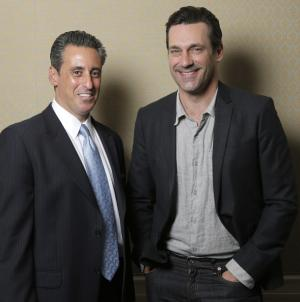 """This Sunday, April 13, 2014 photo shows J. B. Bernstein, left, posing with actor Jon Hamm who plays him in the film """"Million Dollar Arm,"""" in Los Angeles. To portray Bernstein, the sports agent behind the signing of the first two Indian Major Leaguers,"""" Hamm had to act like a noble guy in Disney's """"Million Dollar Arm"""" instead of the cutthroat ad exec he embodies on TV's """"Mad Men."""" The movie releases in U.S. theaters on Friday, May 16, 2014. (Photo by Todd Williamson/Invision/AP)"""