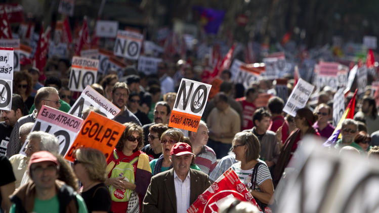 People hold banners against cuts during a demonstration in Madrid, Spain, Sunday, Oct. 7, 2012. Thousands of people called by 150 organizations are marching in 56 Spanish cities to protest punishing austerity cuts they say will only increase unemployment and job insecurity.  (AP Photo/Alberto Di Lolli)