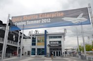 A banner promotes space shuttle Enterprise's arrival and upcoming display at the Intrepid Sea, Air & Space Museum in New York City.